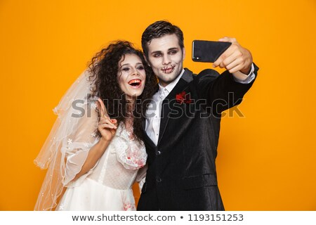 pretty creepy man and woman in wedding costumes making selfie on smartphone isolated stock photo © deandrobot