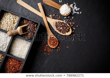 Wooden box of raw organic red rice on white background. Healthy food.  Stock photo © DenisMArt