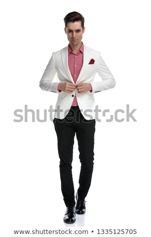 young cool elegant man walking and buttoning his coat stock photo © feedough