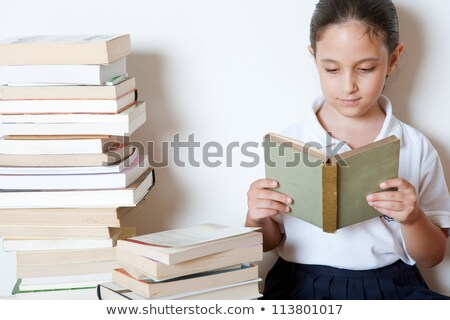 Female Student In Uniform Sitting On Pile Of Books Reading Stock photo © monkey_business