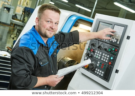 Worker operating a CNC lathe in factory Stock photo © Kzenon