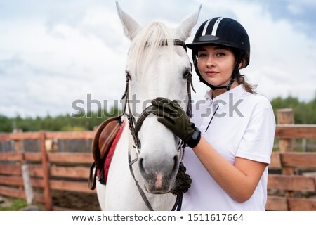 Calm woman in white polo shirt and equestrian outfit embracing purebred horse Stock photo © pressmaster