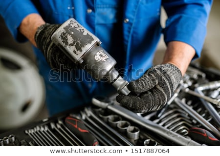 Gloved repairman in workwear putting one of nozzles on metallic drill Stock photo © pressmaster