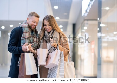 Happy young spouses in coats and scarves looking at what they bought Stock photo © pressmaster