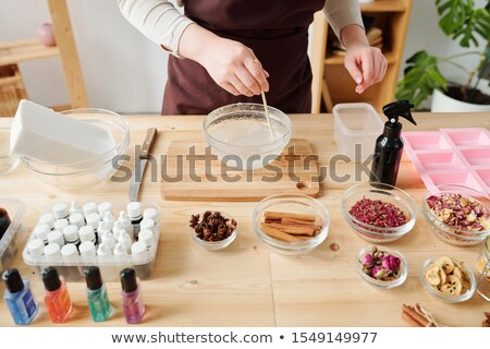 Young female in apron standing by table and mixing liquid soap mass in glassware Stock photo © pressmaster