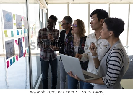 Side view of standing mixed race business colleagues discussing over chart in modern office Stock photo © wavebreak_media