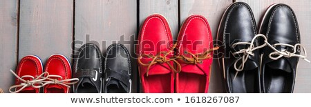 Family boat shoes on wooden background. Four pair of red and black boat shoes on grey desk with rope Stock photo © Illia