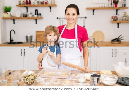 cute smiling boy with sifter and his mother with rolling pin standing by table stock photo © pressmaster