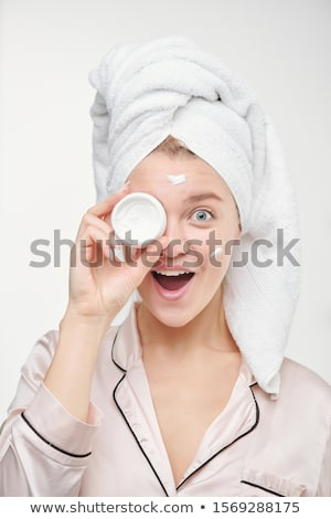 Pretty young ecstatic female with towel on head holding jar of facial cream Stock photo © pressmaster
