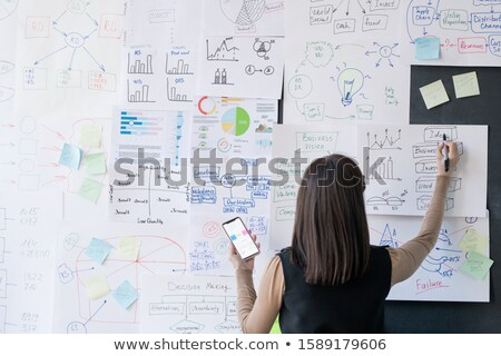 Back view of female coach or economist analyzing financial information on papers Stock photo © pressmaster