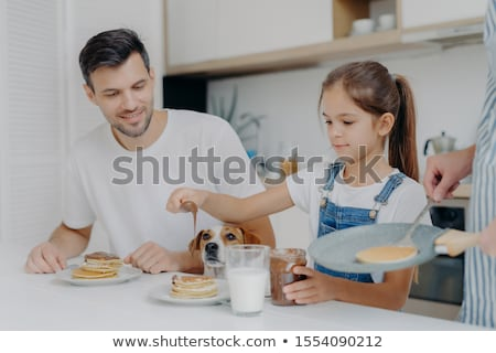 Photo of little girl in denim dungarees adds chocolate to pancakes, has breakfast together with dad  Stock photo © vkstudio