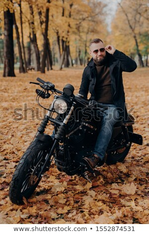 Vertical image of thoughful biker wears sunglasses, rides motorbike in park, poses on street, wears  Stock photo © vkstudio