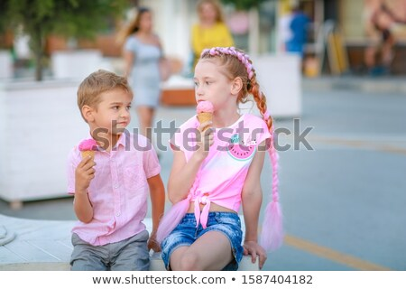 The children a boy and a girl sat down to rest and eat a little sweet food Stock photo © ElenaBatkova