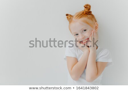 Shy pretty girl has two hair buns, touches cheeks gently, smiles happily, has freckles, hears someth Stock photo © vkstudio