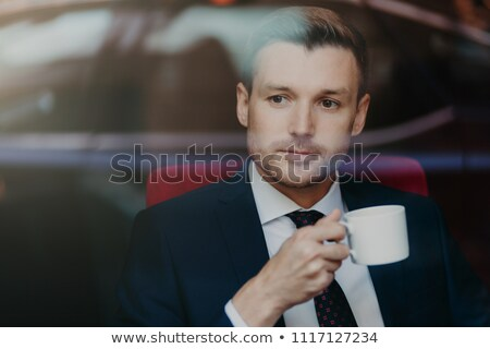 Photo of successful prosperous male entrepreneur with stubble, thinks about something, wears formal  Stock photo © vkstudio