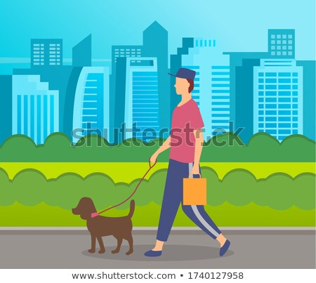 Stylish guy in cap, holding bag walking with dog in urban park, city buildings at background Stock photo © robuart