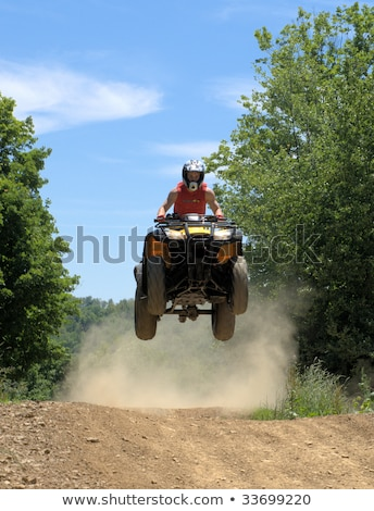 Teen riding ATV in mountains Stock photo © ravensfoot