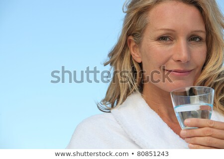 attractive blonde haired woman with no make up on and drinking a glass of water stock photo © photography33