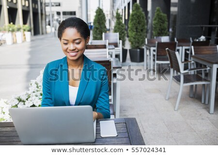 portrait of young business woman sitting relaxed at outdoor cafe stock photo © hasloo