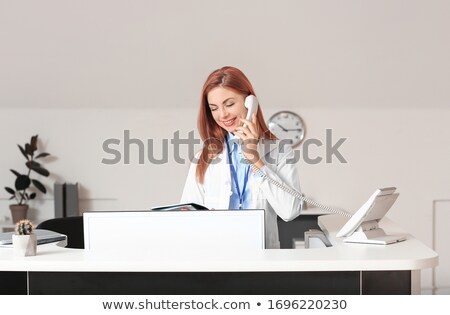 woman working as nurse in clinic and speaking on telephone stock photo © diego_cervo