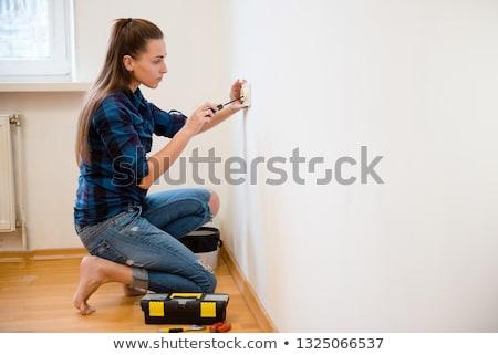 Stockfoto: Female Electrician Installing A Wall Socket
