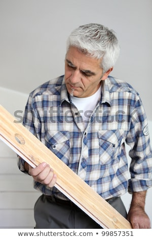 Grey-haired man holding an d examining plank of wood Stock photo © photography33