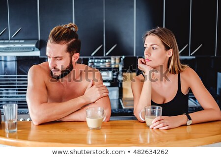 Stockfoto: Exhausted Couple Drinking Coffee In A Kitchen