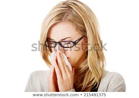 A woman with a cold or allergy wiping or blowing her nose.  Stock photo © dacasdo