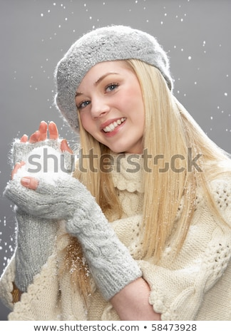 Young Woman Wearing Warm Winter Clothes And Hat Holding Snowball Stock photo © monkey_business