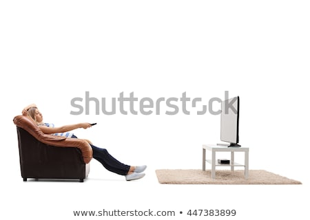 Young woman sitting on a chair with a remote control on white background studio stock photo © ambro