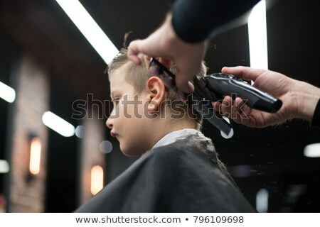 Closeup portrait of a man cuts hair with hair clipper on back of the head Stock photo © deandrobot