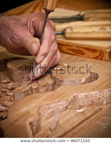 Carpenter hand carving wood with care stock photo © jordanrusev