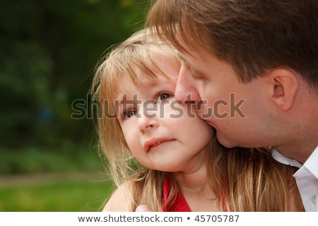 Sad little girl cries in park. Father calms her kissing on cheek.  Close up. stock photo © Paha_L