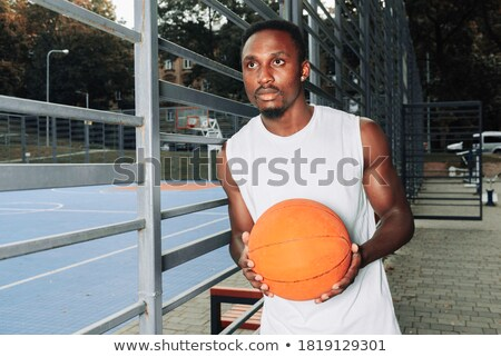 portrait of a beautiful young muscular man leaning against a fence stock photo © zurijeta