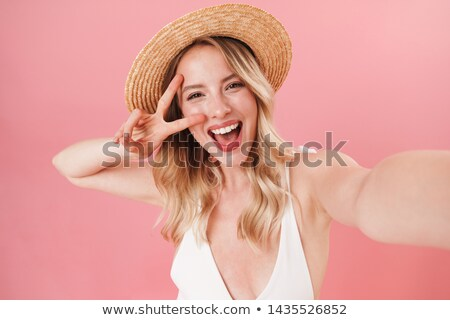 Young pretty girl in swimsuit standing and showing peace gesture Stock photo © deandrobot