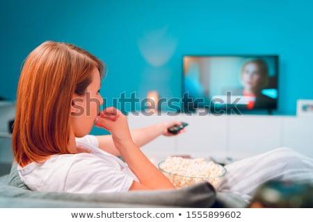 Photo stock: Ne · jeune · femme · allongée · sur · son · canapé · à · regarder · la · télévision