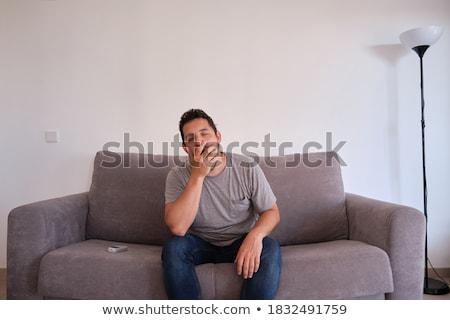 Somnolent jeune homme séance canapé travaux Photo stock © lightpoet