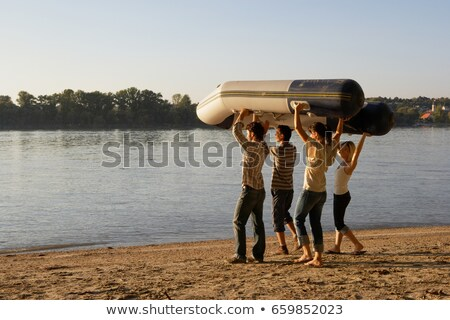 four friends carrying a raft on a beach stock photo © is2