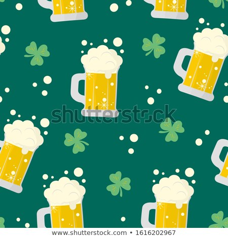 glass of green beer with shamrock and horseshoe stock photo © dolgachov