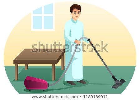 Muslim Man Vacuuming The Carpet At Home Stockfoto © Artisticco
