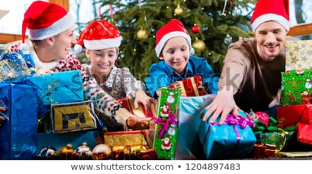 Mum, dad and sons on X-mas during handing out of presents Stock photo © Kzenon