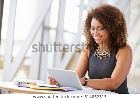 smiling african woman using a tablet in office stock photo © boggy
