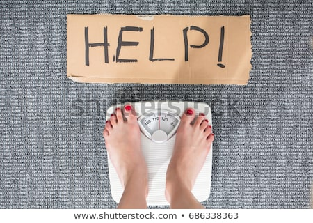 Help Sign With Woman's Feet On Weighing Scale Stock photo © AndreyPopov