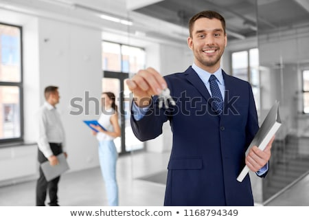 smiling realtor with keys and folder at new office stock photo © dolgachov