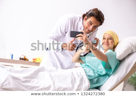 Сток-фото: Young handsome doctor visiting female oncology patient