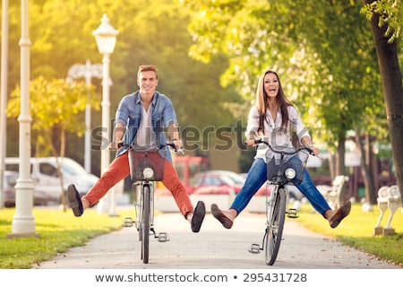Foto stock: young beautiful woman riding a bicycle in a park. Active people. Outdoor
