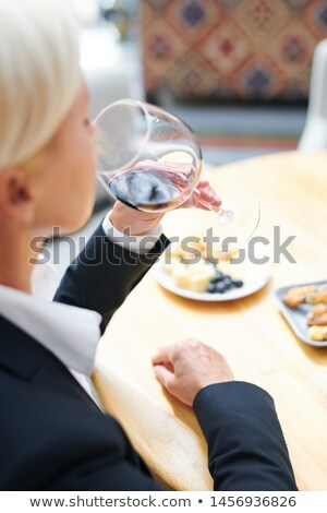 Professional mature female sommelier evaluating flavor of red cabernet Stock photo © pressmaster