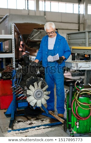 Senior master of car service of maintenance reading paper with instructions Stock photo © pressmaster