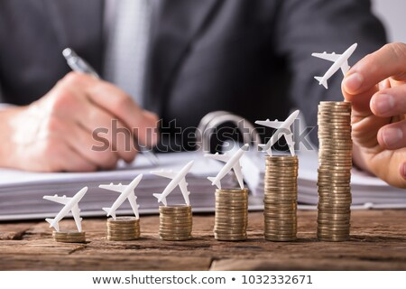 Human Hand Placing Small Airplane On Increasing Stacked Coins Stock photo © AndreyPopov