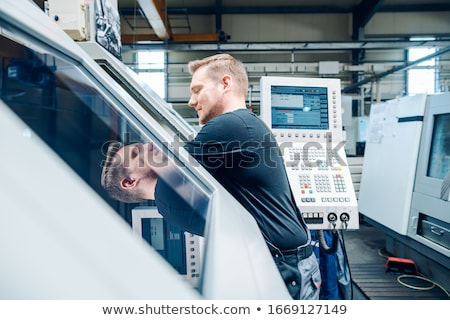 Worker resetting a cnc lathe machine in manufacturing factory Stock photo © Kzenon